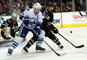 Photo - Vancouver Canucks center Alex Burrows (14) looks for a shot on-goal as Dallas Stars defenseman Trevor Daley (6) defends during the second period of an NHL hockey game on Thursday, April 18, 2013 in Dallas. (AP Photo/ Michael Mulvey)