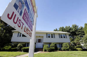 Photo - In this Wednesday, Sept. 18, 2013 photo a for sale sign hangs in front of a house in Walpole, Mass. U.S. home sales rose  in August 2013 to the highest level since February 2007 as buyers rushed to close deals before interest rates rise further.( AP Photo/Steven Senne)