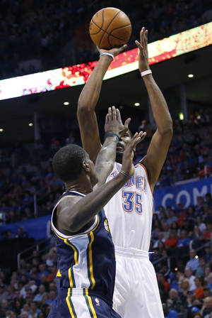 Photo - Oklahoma City Thunder forward Kevin Durant (35) shoots over Utah Jazz forward Marvin Williams (2) in the first quarter of an NBA basketball game in Oklahoma City, Sunday, March 30, 2014. Oklahoma City won 116-96. (AP Photo/Sue Ogrocki)