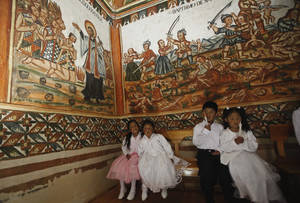 Photo - Children wait te be baptized inside the Sistine Chapel of Los Andes in Curahuara de Carangas, Oruro department, 260 km. (160 miles) south from La Paz, Bolivia, Saturday, Dec. 8, 2012.  The colonial-era house of worship known in Bolivia as the Sistine Chapel of the Andes was filled with flowers over the weekend for those celebrating two weddings and seven baptisms on the wind swept mountain plateau.(AP Photo/Juan Karita)