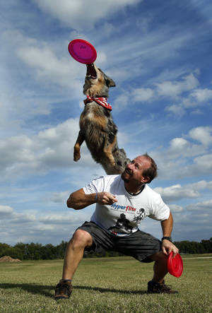Photo - Lee Fairchild and his dog, Gracie, demonstrate their dog disc skills recently in  Goldsby. Photo by Steve Sisney, The Oklahoman