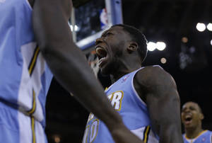 Photo - Denver Nuggets' Nate Robinson, center, celebrates a score against the Golden State Warriors during the second half of an NBA basketball game on Wednesday, Jan. 15, 2014, in Oakland, Calif. (AP Photo/Ben Margot)
