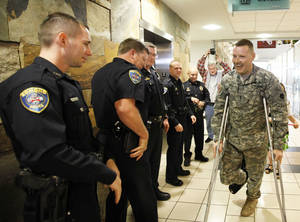 Photo - MILITARY / RETURN: Edmond Police officer Kyle Stoy and Oklahoma National Guard soldier returns home at Will Rogers World Airport in  Oklahoma City, Thursday, March 22, 2012. Photo by Sarah Phipps, The Oklahoman.