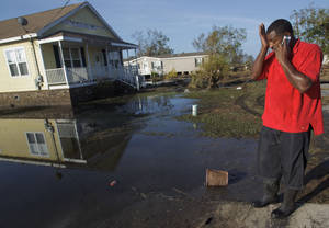 Photo -   Ron Steward wipes his brow next to the house of his mother, Clara Williams, in Ironton, La., which was flooded from Hurricane Isaac, near Louisiana Hwy 23 in Plaquemines Parish, Monday, Sept. 3, 2012. The house was built seven years ago after her previous home was destroyed by Hurricane Katrina. (AP Photo/Matthew Hinton)
