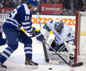 Photo - Vancouver Canucks goaltender Roberto Luongo makes a save on Toronto Maple Leafs left winger Joffrey Lupul during the second period of an NHL hockey game, Saturday, Feb. 8, 2014 in Toronto. (AP Photo/The Canadian Press, Frank Gunn)