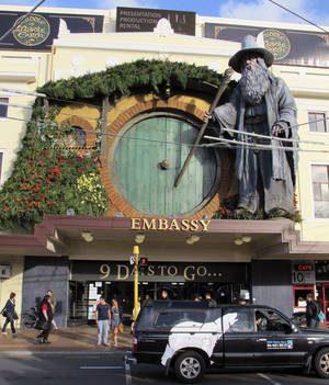 "Photo -   People walk by the Embassy Theater where a giant statue of the character Gandalf from the upcoming movie ""The Hobbit: An Unexpected Journey"" overlooks the passersby in Wellington, New Zealand, Monday, Nov. 19, 2012. Animal wranglers involved in the making of ""The Hobbit"" movie trilogy say the production company is responsible for the deaths of up to 27 animals, largely because they were kept at a farm filled with bluffs, sinkholes and other ""death traps."" (AP photo/Nick Perry)"