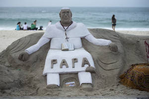Photo - A sand sculpture that resembles Pope Francis sits on Copacabana beach, Rio de Janeiro, Brazil on Sunday, July 21, 2013.  Pope Francis, the 76-year-old Argentine who became the church's first pontiff from the Americas in March, will return Monday to the embrace of Latin America to preside over the Roman Catholic Church's World Youth Day festival.(AP Photo/Victor R. Caivano)
