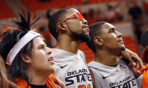 Photo - From left, OSU sophomore Brian Bowling, player Michael Cobbins (20) and player Le'Bryan Nash (2) sing the alma mater after the Bedlam men's college basketball game between the Oklahoma State University Cowboys and the University of Oklahoma Sooners at Gallagher-Iba Arena in Stillwater, Okla., Monday, Jan. 9, 2012. OSU beat OU, 72-65. Photo by Nate Billings, The Oklahoman