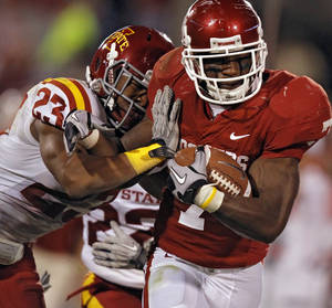 Photo - Oklahoma's DeMarco Murray (7) is hit by Iowa State's Leonard Johnson (23) during the first half of the college football game between the University of Oklahoma Sooners (OU) and the Iowa State Cyclones (ISU) at the Glaylord Family-Oklahoma Memorial Stadium on Saturday, Oct. 16, 2010, in Norman, Okla.  Photo by Chris Landsberger, The Oklahoman