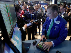 Photo - Specialist Edward Zelles, foreground, works with traders at his post on the floor of the New York Stock Exchange Monday, June 2, 2014. Stocks were moving slightly lower in early trading Monday following the release of a closely watched report that showed an unexpected slowdown in U.S. manufacturing last month. The market is coming off record highs last week. (AP Photo/Richard Drew)