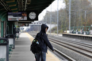 Photo -   Josh Lin, 21, looks for an New Jersey Transit commuter train as he stands alone on the platform Thursday, Nov. 1, 2012, in Princeton Junction, N.J. There still is no train service after Monday's storm surge from superstorm Sandy knocked out power, caused flooding and toppled trees. Planes were getting up to speed faster than trains and automobiles in the storm-stricken Northeast. The region's major airports were all open once New York's LaGuardia resumed flights Thursday morning. While there were additional canceled flights and the tri-state air space was still relatively empty, flying was closer to normalcy than moving by rail, subway or car. (AP Photo/Mel Evans)