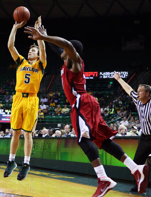 Photo - Baylor guard Brady Heslip (5) connects for a three-point shot over Louisiana Lafayette guard Kevin Brown (31), right, in the first half of an NCAA college basketball game, Sunday, Nov. 17, 2013, in Waco, Texas. (AP Photo/Waco Tribune Herald, Rod Aydelotte)