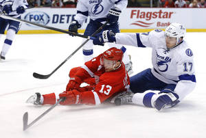 Photo - Detroit Red Wings center Pavel Datsyuk (13), of Russia, shoots from the ice as Tampa Bay Lightning center Alex Killorn (17) defends in the second period of an NHL hockey game in Detroit Sunday, Dec. 15, 2013. (AP Photo/Paul Sancya)