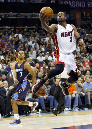 Photo - Miami Heat's Dwyane Wade (3) drives past Charlotte Bobcats' Ramon Sessions (7) after being fouled during the second half of an NBA basketball game in Charlotte, N.C., Wednesday, Dec. 26, 2012. Miami won 105-92. (AP Photo/Chuck Burton)