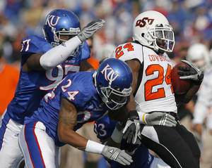 photo - Oklahoma State&#039;s Kendall Hunter (24) is brought down by Kansas&#039; Richard Johnson Jr. (97) and Kansas&#039; Taylor Lee (24)during the college football game between Oklahoma State (OSU) and Kansas (KU), Saturday, Nov. 20, 2010 at Memorial Stadium in Lawrence, Kan. Photo by Sarah Phipps, The Oklahoman 
