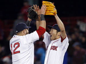 Photo - Boston Red Sox closer Koji Uehara, right, celebrates with first baseman Mike Napoli (12) after the Red Sox defeated the New York Yankees 5-1 in a baseball game at Fenway Park in Boston, Wednesday, April 23, 2014. (AP Photo/Elise Amendola)