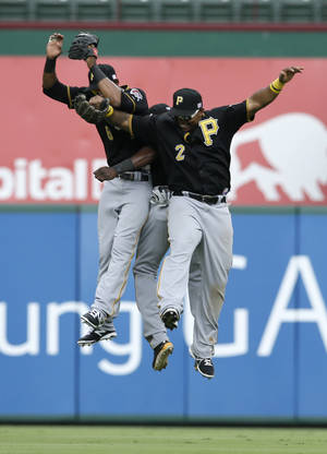 Photo - Pittsburgh Pirates' Marlon Byrd (2), Starling Marte, left, and Felix Pie, rear, celebrate following a baseball game against the Texas Rangers, Wednesday, Sept. 11, 2013, in Arlington, Texas. The Pirates won 7-5, sweeping the Rangers in a three-game series. (AP Photo/Tony Gutierrez)