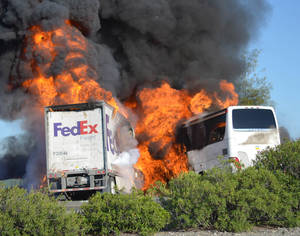 Photo - FILE - In this Thursday, April, 10, 2014, file photo, massive flames engulf a tractor-trailer and a tour bus just after they collide on Interstate 5, near Orland, Calif. The mother of a 17-year-old honors student who was among 10 people killed in the fiery Northern California bus crash sued FedEx on Tuesday, April 22, 2014, alleging that its trucks have a history of catching fire. (AP Photo/Jeremy Lockett, File)