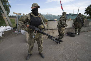 Photo - Pro-Russian armed militants guard a checkpoint blocking the major highway which links Kharkiv, outside Slovyansk, Ukraine, Saturday, May 24, 2014. Ukrainians vote Sunday in an early presidential election that could be a crucial step toward resolving the country's crisis, but separatists in the east are threatening to block the vote. The election, which comes six months after the outbreak of protests that led to the president's ouster and a deepening chasm between pro-Europe and pro-Russia Ukrainians, aims to unify the fiercely divided country or at least discourage further polarization.(AP Photo/Alexander Zemlianichenko)