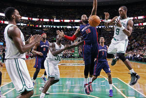 Photo - Boston Celtics' Rajon Rondo (9) passes in front of Detroit Pistons' Greg Monroe (10) in the first quarter of an NBA basketball game in Boston, Sunday, March 9, 2014. (AP Photo/Michael Dwyer)