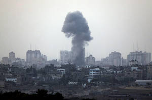 Photo -   A plume of smoke is seen over central Gaza Strip, after an airstrike by Israeli forces, as seen from the Israel Gaza border, Monday, Nov. 19, 2012. Israeli aircraft struck crowded areas in the Gaza Strip and killed a senior militant with a missile strike on a media center Monday, driving up the Palestinian death toll to 96, as Israel broadened its targets in the 6-day-old offensive meant to quell Hamas rocket fire on Israel. (AP Photo/Lefteris Pitarakis)