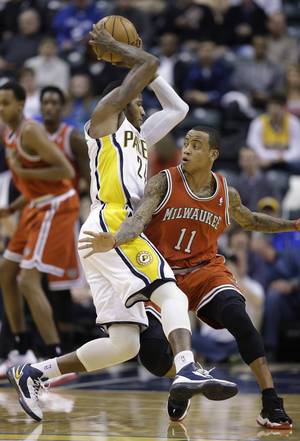 photo - Indiana Pacers' Paul George (24) is fouled by Milwaukee Bucks' Monta Ellis (11) during the first half of an NBA basketball game Saturday, Jan. 5, 2013, in Indianapolis. (AP Photo/Darron Cummings)