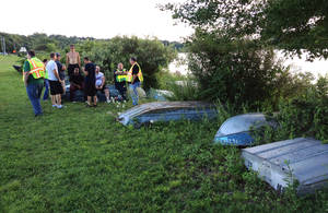 Photo -   In this Aug. 6, 2012, police gather on the shore of Lake Gleneida in Carmel, New York, where a woman drowned, and and a 6-year-old clinging to the floating corpse was rescued by three people fishing in a rowboat. Authorities said an autopsy was planned to determine if the woman drowned or suffered some kind of medical emergency while wading with the girl in the water. (AP Photo/The Journal News, Alexander Weisler) NEW YORK METRO OUT, NEWSDAY DIGITAL OUT