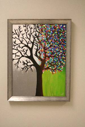 Photo - A painting of a tree hanging in The Children's Center depicts the healing process, from trauma, with barren branches on the left, to wellness, shown with brightly colored leaves, on the right. PHOTO BY CHARLOTTE LANKARD, FOR THE OKLAHOMAN. <strong></strong>