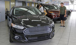 Photo - In this photo taken Aug. 21, 2014, Orestes Perez, right, and his niece Yanuska Perez, check a 2013 Ford Fusion SE at a local dealership in Hialeah, Fla. The Commerce Department reports on business orders for durable goods in July on Tuesday, Aug. 26, 2014. (AP Photo/Alan Diaz)