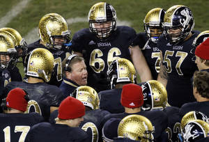 "Photo -   FILE - In this Oct. 6, 2012, file photo, Notre Dame head coach Brian Kelly, center left, talks to his team during the second half of an NCAA college football game against Miami at Soldier Field in Chicago. About the only thing the Irish haven't done yet this season is rally from behind to win. The Irish have been able to ignore what coach Kelly refers to as the ""noise"" so far, but it keeps getting louder with every victory.(AP Photo/Charles Rex Arbogast, File)"