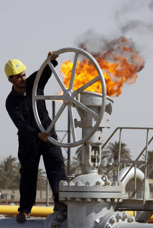 Photo - FILE - In this file photo of Friday, July 17, 2009, an Iraqi worker operates valves at the Nahran Omar oil refinery in Zubair near the city of Basra, 340 miles (550 kilometers) southeast of Baghdad, Iraq. The turmoil in Iraq has thrown the OPEC member's ambitious plans to boost oil production into doubt, threatening to crimp its most vital economic lifeline. Northern oil fields imperiled by the militants' advance have been shut down, and companies have begun evacuating workers elsewhere in the country. Iraq's Kurdish minority has moved to solidify control over the northern oil-rich city of Kirkuk and other disputed areas, weakening Baghdad's claims to the energy riches buried beneath while bolstering the Kurds' aspirations of greater autonomy. (AP Photo/Nabil al-Jurani, File)