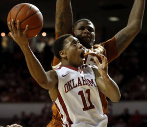 Photo - OU's Isaiah Cousins shoots past Texas' Cameron Ridley during Saturday's matchup.