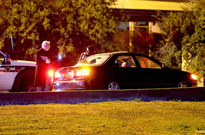 Photo - New Orleans police examine a car with a shot-out rear window as they investigate a shooting on the Crescent City Connection which left a man and an infant dead on Wednesday, Nov. 13, 2013. New Orleans police spokesman Officer Frank B. Robertson III says the shooting was an apparent ambush that occurred while the man was driving.  (AP Photo/Michael DeMocker, Nola.com / The Times-Picayune)