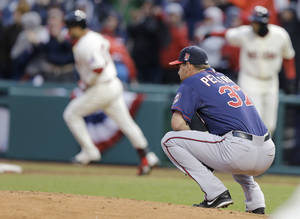 Photo - Minnesota Twins starting pitcher Mike Pelfrey, right, watches as Cleveland Indians' Nick Swisher, left, runs the bases after hitting a two-run home run in the sixth inning of a baseball game, Friday, April 4, 2014, in Cleveland. Lonnie Chisenhall scored. (AP Photo/Mark Duncan)