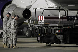 photo -   Chaplain Col. Dennis Goodwin, left, directs a prayer over the transfer case containing the remains of Army Capt. Bruce K. Clark of Spencerport, N.Y., upon arrival at Dover Air Force Base, Del. on Thursday May 3, 2012. The Department of Defense announced the death of Clark who was supporting Operation Enduring Freedom in Afghanistan. (AP Photo/Jose Luis Magana)