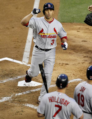 Photo -   St. Louis Cardinals' Carlos Beltran (3) crosses home plate after hitting a grand slam, his second home run of the baseball game, against the Arizona Diamondbacks during the second inning Tuesday, May 8, 2012, in Phoenix. At home plate are teammates Matt Holliday (7) and Jon Jay (19). (AP Photo/Matt York)