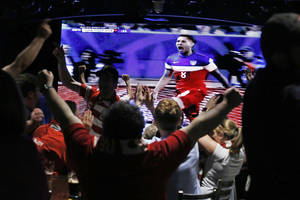 Photo - Soccer fans react at a viewing party at a restaurant in Pittsburgh after watching the United States score in the opening minute of play against Ghana in a World Cup soccer match in Brazil. Clint Dempsey (8) scored the fastest goal by an American in World Cup history, putting the United States ahead after 32 seconds of its opener against Ghana on Monday. June 16, 2014. (AP Photo/Gene J. Puskar)