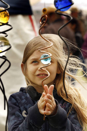 """Photo - Sophie Martin, 9, looks at an ornamental piece at the """"Dances with Nature"""" booth at the May Fair Arts Festival in Norman. PHOTO BY STEVE SISNEY, THE OKLAHOMAN <strong>STEVE SISNEY</strong>"""
