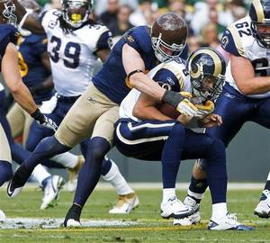 Photo - Green Bay Packers inside linebacker A.J. Hawk sacks St. Louis Rams quarterback Sam Bradford during the first half of an NFL football game Sunday in Green Bay, Wis. (AP Photo/Jeffrey Phelps)