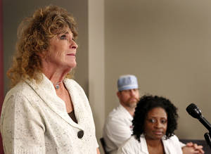 Photo - As doctors look on Monday during a news conference at the Samis Education Center in Oklahoma City,  Tammy Cauthron discusses the surgical process of reconstructing the face of her son, Taron Pounds. Pounds, 22, suffered major injuries to his face, eye, neck and chest when a fireworks mortar blew up in his face at a family event in July. Photo by Jim Beckel, The Oklahoman