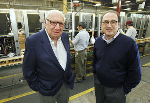 Photo - Jack Golsen, CEO (left) and Barry Golsen, Chairman of LSB Industries, stand in front of one of the assembly lines at ClimateMaster in Oklahoma City, OK, Monday, Oct. 17, 2011. By Paul Hellstern, The Oklahoman