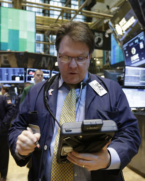 Photo - FILE - Trader Stephen McSherry works on the floor of the New York Stock Exchange in this March 12, 2014 file photo. Markets in Europe traded in fairly narrow ranges Thursday April 10, 2014 as the successful return of Greece to bond markets following a four-year absence helped further steady the nerves following a turbulent start to the week. (AP Photo/Richard Drew)