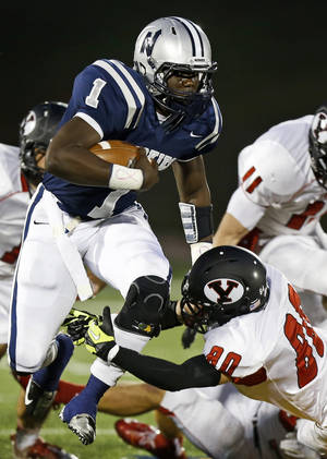 photo - Edmond North's Michael Farmer tries to leap past Yukon's Zayne Nave during their high school football game at Wantland Stadium in Edmond, Okla., Thursday, October 4, 2012. Photo by Bryan Terry, The Oklahoman