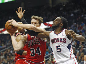 Photo - Atlanta Hawks small forward DeMarre Carroll (5) and Chicago Bulls small forward Mike Dunleavy (34) fight for a rebound in the first half of an NBA basketball game  Tuesday, Feb. 25, 2014, in Atlanta. (AP Photo/John Bazemore)