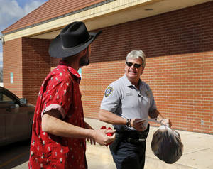 Photo -  Deputy Marshal Thomas Maassen carries a bag containing the personal belongings of a man he picked up at the Bethany Police Department after Bethany officers had detained him and discovered he had outstanding warrants in Oklahoma City. PHOTO BY JIM BECKEL, THE OKLAHOMAN  <strong>Jim Beckel -   </strong>