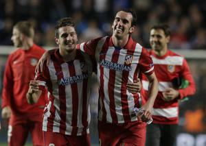 Photo - Atletico's Koke, left and teammate Atletico's Diego Godin celebrate in front of their fans after defeating Chelsea in the Champions League semifinal second leg soccer match between Chelsea and Atletico Madrid at Stamford Bridge stadium in London, Wednesday, April 30, 2014. (AP Photo/Matt Dunham)