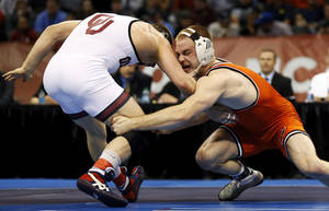 Photo - OSU's Chris Perry wrestles OU's Andrew Howe during the 174-pound championship match in the 2014 NCAA Div. I Wrestling Championships at Chesapeake Energy Arena in Oklahoma City, Saturday, March 22, 2014. Photo by Nate Billings, The Oklahoman