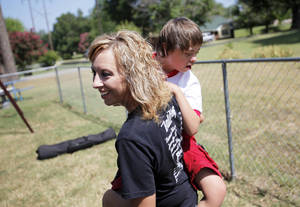Photo - Holli Griggs-Harjo carries her son, Taylor, 11, on July 4 in Seminole.  Photo by Garett Fisbeck, The Oklahoman