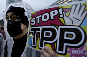 "Photo - A protester holds a placard during a rally against the Trans-Pacific Partnership (TPP) in Tokyo, Tuesday, April 22, 2014. In Japan and elsewhere, there are concerns over making politically difficult market-opening concessions without reassurance that Obama will have the ""fast track"" authority to get congressional approval for TPP. Critics of the plan have balked at granting such power for a trade deal whose contents have been kept largely secret as a precondition for joining. (AP Photo/Shizuo Kambayashi)"