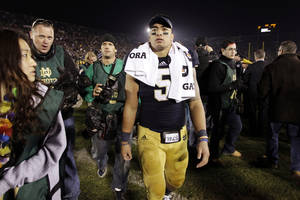photo - FILE - In this Nov. 17, 2012, file photo, Notre Dame linebacker Manti Te'o walks off the field following an NCAA college football game against Wake Forest in South Bend, Ind. A story that Te'o's girlfriend had died of leukemia _ a loss he said inspired him to help lead the Irish to the BCS championship game _ was dismissed by the university Wednesday, Jan. 16, 2013, as a hoax perpetrated against the linebacker. (AP Photo/Michael Conroy, File)